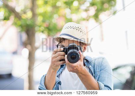 Man wearing hat taking photo outdoors