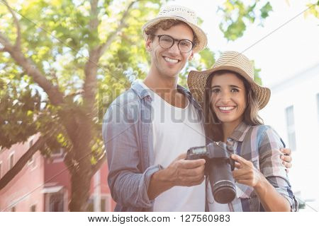 Portrait of happy young couple wearing hat holding camera