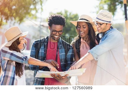 Group of friends looking at map and discussing outdoors