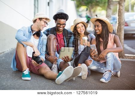 Group of friends using digital tablet and mobile phone on roadside