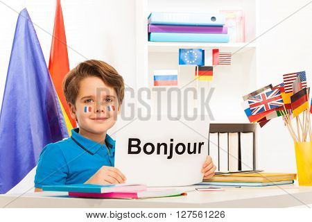 Boy learning French sitting at the desk in the classroom holding sheet of paper with printed word bonjour