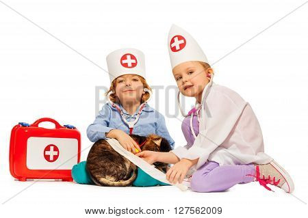 Two kids-veterinarians bandaging a paw to a cat, isolated on white background
