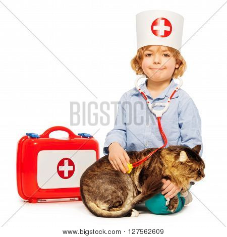 Boy 5 years old playing veterinarian with stethoscope, medicine box and cat, isolated on white background
