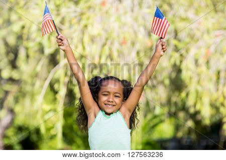 Young girl showing usa flag at park