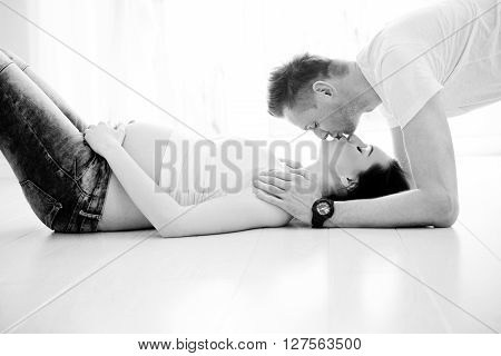 Future Dad Kissing Pregnant Wife Lying On The Floor