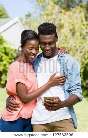 Happy couple looking their smartphone at park
