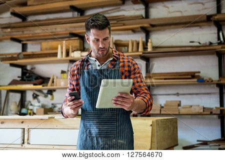 Carpenter reading a manual on the one hand and the other is taking his phone in a dusty workshop