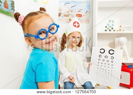 Cute little girl in blue toy glasses at the ophthalmologist room