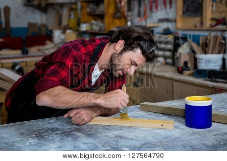 Carpenter painting a piece of wood on his workshop