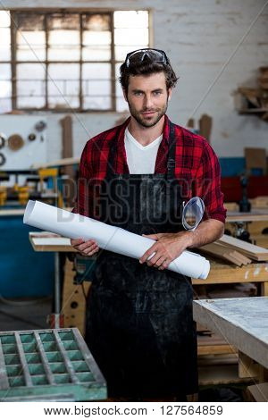 Carpenter with plans smiling on his workshop