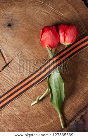 Victory day St. George ribbon and red tulips on wooden background