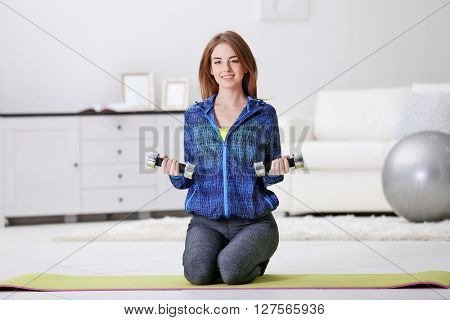 Beautiful young girl doing exercises with dumbbells at home