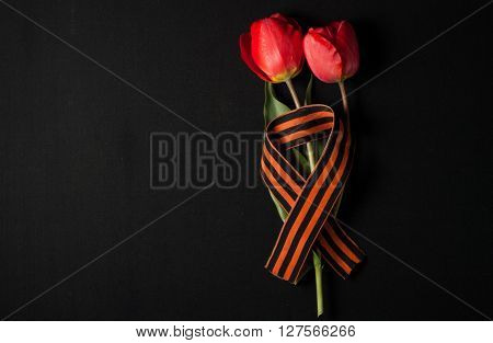 May 9: St. George ribbon and red tulips on a black background