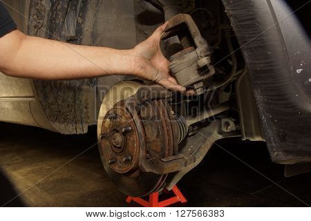 Car mechanic verifying brake system on automobile