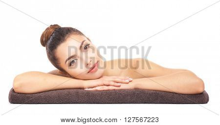 Beautiful young girl lying on brown towel, isolated on white