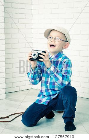 Little boy in a cap photographs. Sitting and photographs
