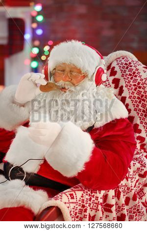 Santa Claus sitting with headphones sitting in comfortable rocking chair at home