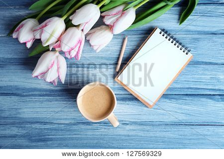 Bouquet of fresh tulips with cup of coffee and notebook on blue wooden background