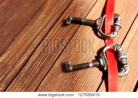 Vintage keys with a red ribbon on a wooden background