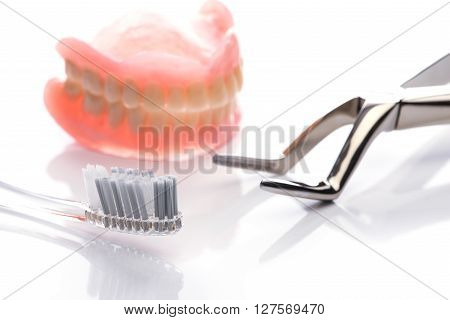 Teeth Model With Toothbrush And Forceps On White Background