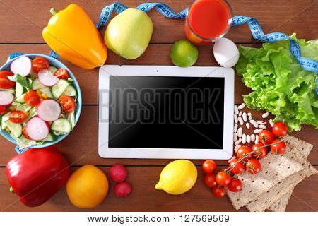 Fresh fruits, vegetables and tablet on wooden table, top view
