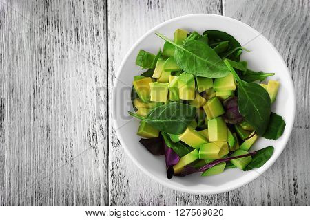 Cubes of fresh avocado on wooden table, top view