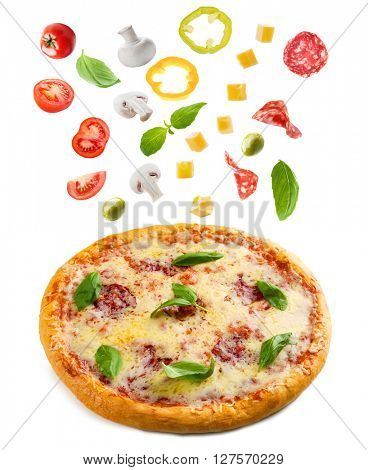 Tasty pizza with falling vegetables and pieces of salami, isolated on white