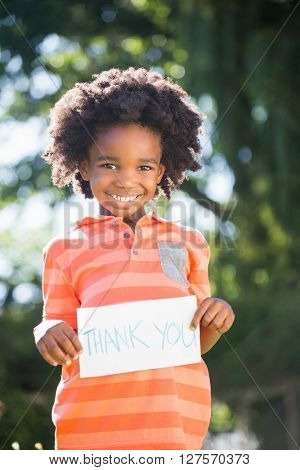 boy is holding a thank you sign in a park