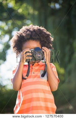 Boy is taking pictures in a park