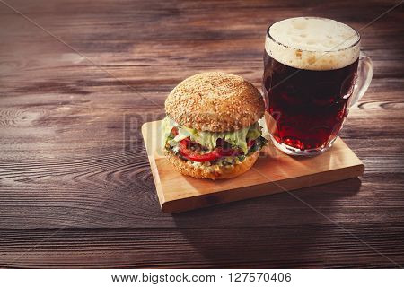 Glass mug of dark beer with hamburger on wooden table. Retro stylization