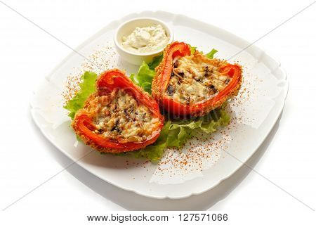 multicolor stuffed bell pepper filled with ground meat, rice, onion and parsley on white plate