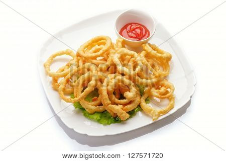 Heap of deep fried onion or calamari rings with chilli dip  on white.