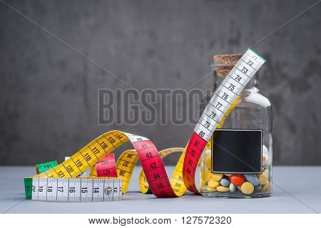 A Bottle Of Diet Pills With Measuring Tape