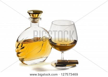 Bottle and a snifter of brandy with a chocolate on a white background