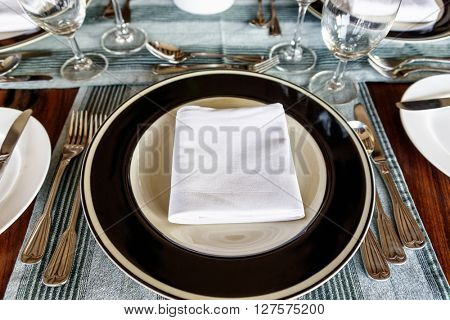 First person perspective view on neatly arranged dining table setting with folded napkin in middle of plate with utensils on sides