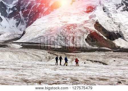 Group of Mountain Climbers with High Altitude Boots and Clothing Crossing Ice Section During Ascent of Alpine Expedition in Asia Mountain Area Sun Shining