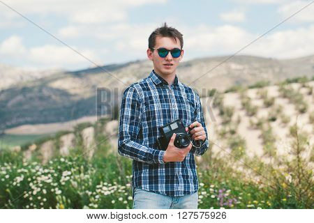Man posing with an old vintage camera in the countryside.
