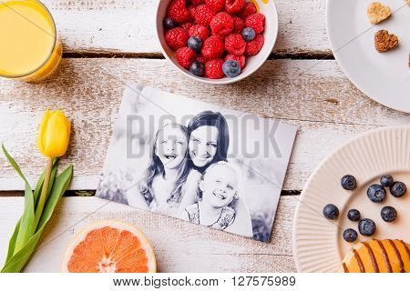 Mothers day composition. Black-and-white picture of mother with her daughters and a breakfast meal. Studio shot on wooden background.