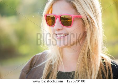 Close up outdoor portrait. Blonde woman posing outdoor in pink sunglasses.