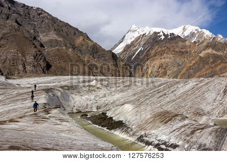 Group of Mountain Climbers Crossing Ice Section along Water Stream Flowing on Glacier Surface During Ascent of Alpine Expedition in Asia Mountain Area