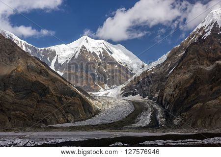 High Mountain View with Majestic Snowbound Peak Brown Steep Rocks and Massive Glacier Flowing Blue Sky and Clouds