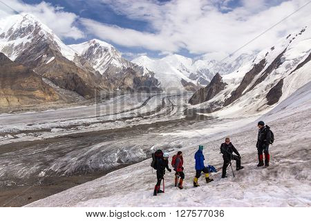 Large Group of People Sport Clothing Climbing Gear High Altitude Boots Going Up Mountain Peaks Sunlight Cloud Sky Massive Glacier Flow on Background