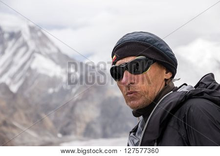 Face of Aged Man Sporty Clothing and Protective Sunglasses with Sceptic Serious Emotion Mountain Landscape Background