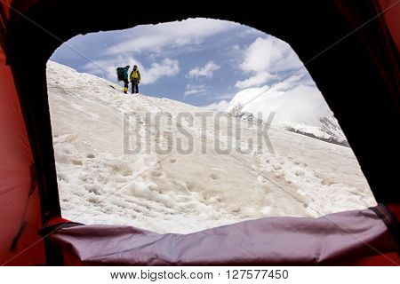 Mountain Expedition Tent Door and Two People Staying on Snow Ridge