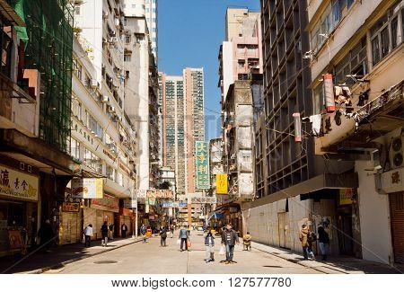 HONG KONG, CHINA - FEB 7, 2016: People on a street with tall scyscrapers with concrete walls in busy district of asian city on February 7, 2016. There are 1223 skyscrapers in Hong Kong.