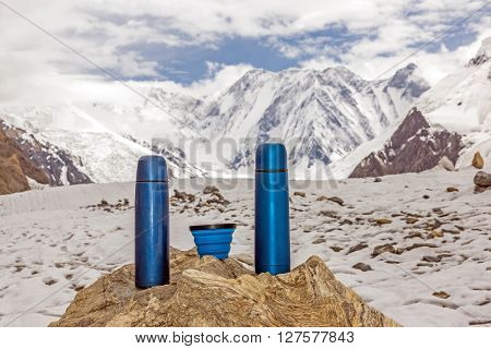 Blue Thermos Flask and Plastic Cup Located on Textured and Colorful Stone with High Altitude Mountain Landscape Background