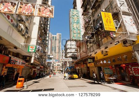 HONG KONG, CHINA - FEB 7, 2016: Street with many shops rustic billboards tall scyscrapers and people walking around on February 7, 2016. There are 1223 skyscrapers in Hong Kong.