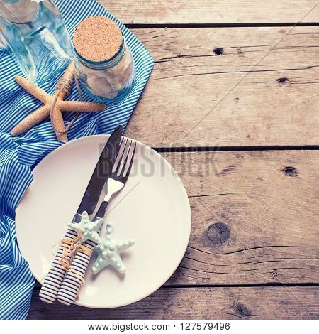 Marine table setting on aged wooden background. Selective focus. Place for text. Square image. Toned image.