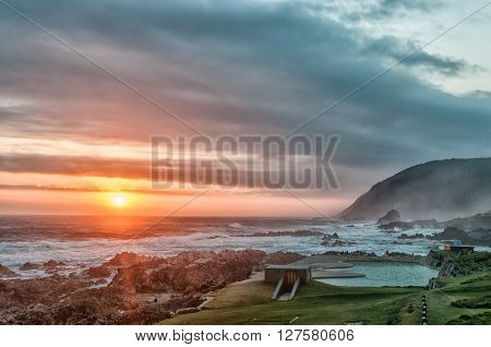 STORMS RIVER MOUTH SOUTH AFRICA - MARCH 1 2016: Unidentified tourists enjoying the sunset at the swimming pool at Storms River Mouth