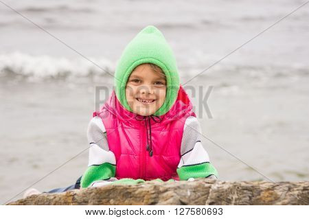 Warmly Dressed Girl With A Smile Peeking Out From Behind A Rock Against The Backdrop Of The Sea